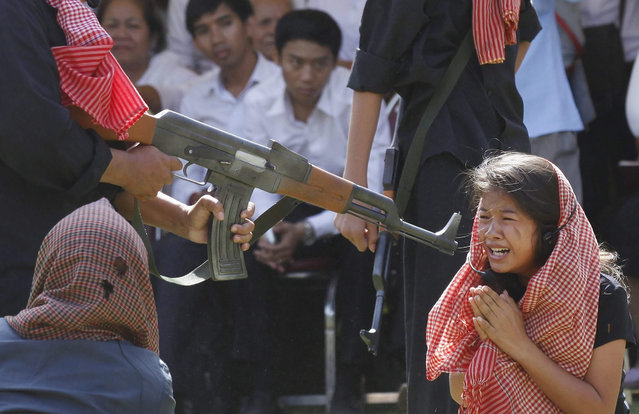 "A scene from the notorious ""Killing Fields"" is re-enacted during a ceremony at the Choeung Ek Genocidal Center in Phnom Penh, Cambodia, 20 May 2015. Cambodia marks the annual Anger Day on 20 May to commemorate the victims who died during the cruel rule of the Khmer Rouge regime from 1975-1979. Some two million Cambodians are estimated to have died by starvation and forced labour or were killed in politically justified executions during the Khmer Rouge regime. (Photo by Mak Remissa/EPA)"