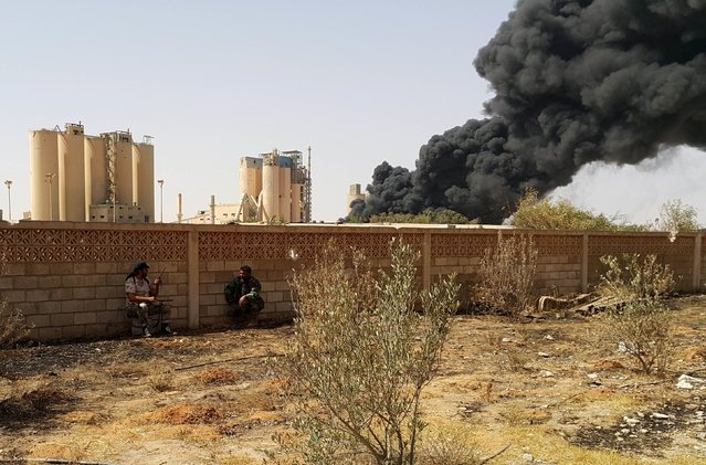 Members of forces loyal to Libya's eastern government sit near the Libyan cement factory during clashes with the Shura Council of Libyan Revolutionaries, an alliance of former anti-Gaddafi rebels who have joined forces with Islamist group Ansar al-Sharia, in Benghazi, Libya April 14, 2016. (Photo by Reuters/Stringer)