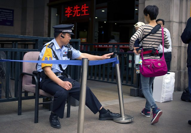 A police officer wearing a revolver holster adjusts a barrier at he sits on duty outside the ticket office at the Beijing Railway Station in Beijing, Wednesday, May 13, 2015. After a policeman shot an unarmed traveler in a train station in northeastern China on May 2, calls for an independent investigation have grown as the Chinese public has become uneasy about the newly granted power for normal police. (Photo by Mark Schiefelbein/AP Photo)