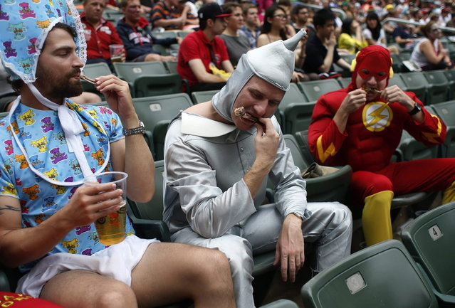Rugby fans eat chicken wings on the last day of the three-day Hong Kong Sevens rugby tournament as part of the Sevens World Series in Hong Kong March 30, 2014. (Photo by Bobby Yip/Reuters)