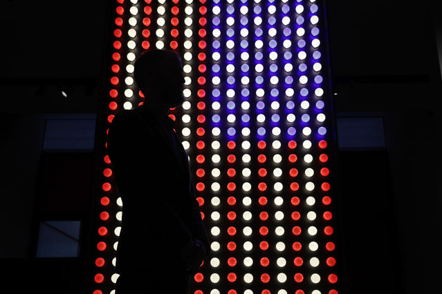 "A British Museum representative poses for photographs next to an illuminated American flag at the entrance of ""The American Dream: pop to the present"" exhibition during a media photocall at the British Museum in London, Monday, March 6, 2017. (Photo by Matt Dunham/AP Photo)"