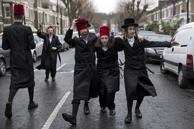 Young Jewish men dance down the street during the annual Jewish holiday of Purim on March 12, 2017 in London, England. (Photo by Dan Kitwood/Getty Images)