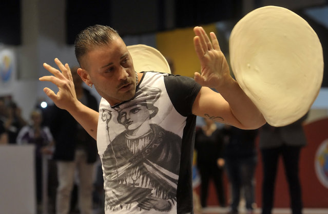 Antonio Fiorillo performs with his dough during the acrobatic pizza event, part of the Pizza World Championships, in Parma, northern Italy, Wednesday, April 9, 2014. (Photo by Marco Vasini/AP Photo)
