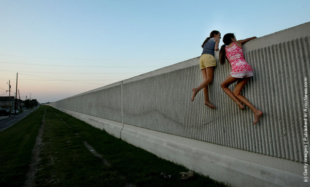 Isabella Lander (L) and Arabella Christiansen climb on the 17th Street Canal levee