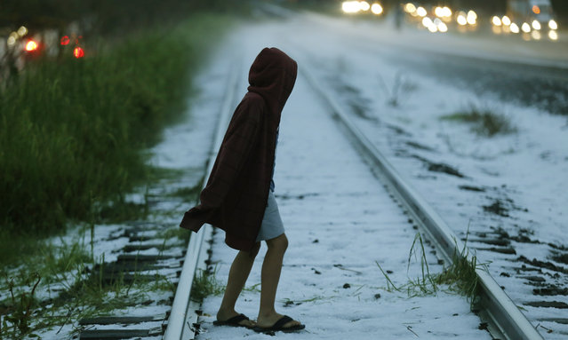 A boy crosses the railway tracks, covered with hail, after a heavy hailstorm that hit the city of Guadalajara, Mexico, 04 August 2019 (issued on 05 August 2019). A heavy hailstorm affected the western city of Guadalajara causing damages in at least 249 houses. (Photo by Francisco Guasco/EPA/EFE)