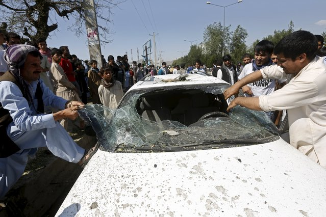 Afghan men remove the broken window of a car at the site of a suicide bomb attack in Kabul, Afghanistan, June 30, 2015. (Photo by Omar Sobhani/Reuters)