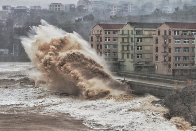 Waves hit a sea wall in front of buildings in Taizhou, China's eastern Zhejiang province on August 9, 2019. China issued a red alert for incoming Super Typhoon Lekima which is expected to batter eastern Zhejiang province early on August 10 with high winds and torrential rainfall. (Photo by AFP Photo/China Stringer Network)