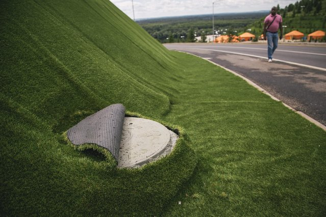 In this photo taken on Sunday, July  5, 2015, a man walks near a Congress Hall which will host SOC (Shanghai Cooperation Organization) and BRICS (Brazil, Russia, India, China and South Africa) summits July 7 to July 9, 2015. A nearby hill has been covered with an artificial grass carpet to give it a better look. (Photo by Vadim Braydov/AP Photo)