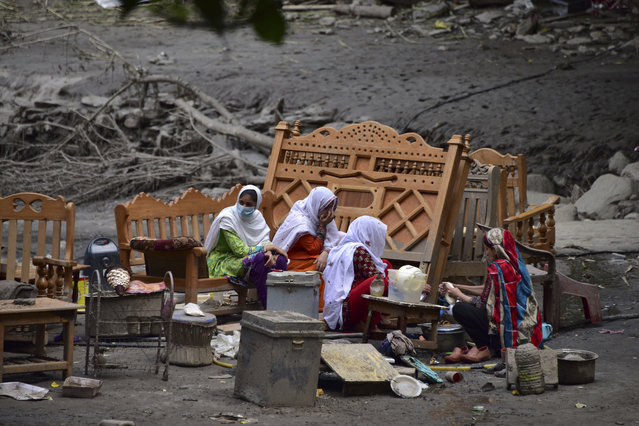 A Pakistani Kashmiri family gather around their belongings outside their damaged house following heavy monsoon rains in Neelum valley, near the Line of Control in Pakistan-controlled Kashmir on July 16, 2019. In Pakistan-administered Kashmir, officials said at least 23 people were killed after heavy rain triggered flash floods and damaged more than 120 houses and 30 shops, while crippling the water and electricity supplies. (Photo by Sajjad Qayyum/AFP Photo)