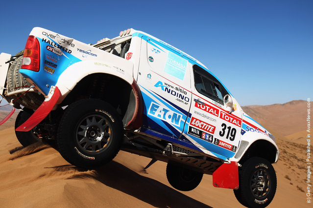Lucio Alvarez of Argentina jumps his Toyota over a sand dune during stage seven of the 2012 Dakar Rally