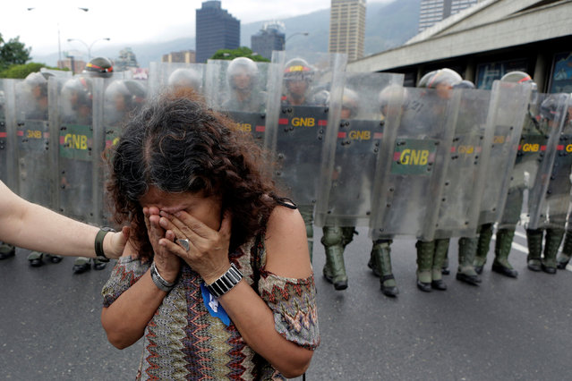 An opposition supporter reacts in front of Venezuelan National Guards in a rally to demand a referendum to remove President Nicolas Maduro in Caracas, Venezuela, May 11, 2016. (Photo by Marco Bello/Reuters)