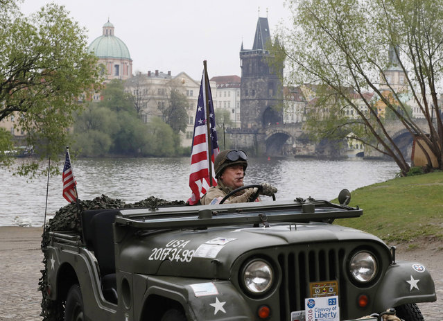 """A history enthusiast dressed in U.S. Army World War II uniform drives his military jeep during the """"Convoy of Liberty"""" that commemorates the 72nd anniversary of the end of the WWII in Prague, Czech Republic, Friday, April 28, 2017. (Photo by Petr David Josek/AP Photo)"""