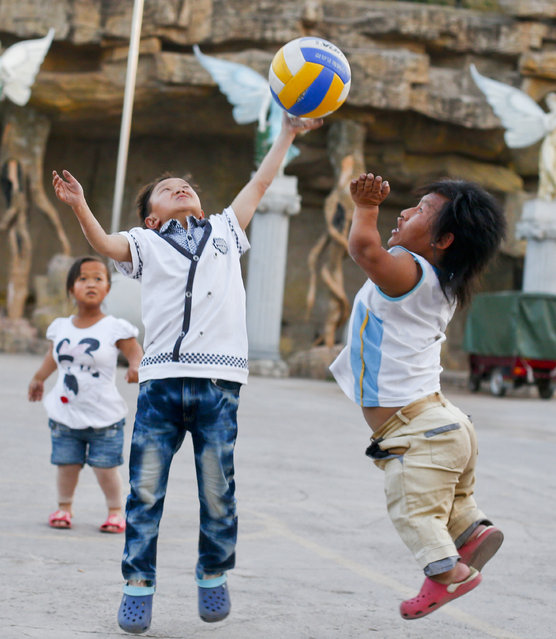 """Cast members of """"Dwarf Empire"""" Yuan Hong Bing (C) and Zhang Jie Min (R) play with a volleyball as 19-year-old Han Zhen Yan looks on outside their dormitories next to the Dwarf Empire theme park outside Kunming, China's Yunnan province, 03 April 2013. (Photo by Diego Azubel/EPA)"""