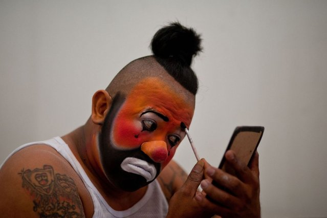 Guatemalan clown Meneito works in his make up, before a workshop during the VI Laugh Festival in San Salvador, El Salvador on May 19, 2014. The Laugh Festival is celebrated by the Latin American clown brotherhood and gathers clowns from Central America to learn and improve their entertainment skills. (Photo by Jose Cabezas/AFP Photo)