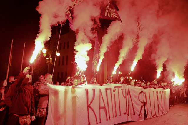 """Activists of Ukrainian nationalists parties burn flares and hold banner reading """"No to capitulation"""" during their protest against approval of so-called Steinmeier Formula in front of Presidential office in Kiev on October 1, 2019. (Photo by Genya Savilov/AFP Photo)"""