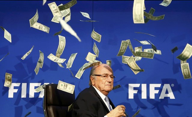 British comedian known as Lee Nelson (unseen) throws banknotes at FIFA President Sepp Blatter as he arrives for a news conference after the Extraordinary FIFA Executive Committee Meeting at the FIFA headquarters in Zurich, Switzerland July 20, 2015. (Photo by Arnd Wiegmann/Reuters)