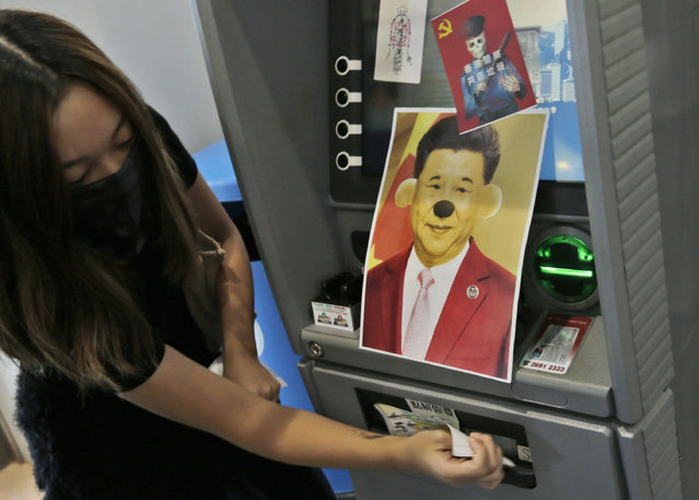 A protester attaches stickers and a defaced portrait of Chinese President Xi Jinping on a Bank of China's ATM machine during an anti-government rally at Hong Kong University of Science and Technology in Hong Kong, Thursday, November 7, 2019. (Photo by Dita Alangkara/AP Photo)
