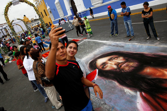 People take a selfie with a sawdust and flower carpet during the feast of Corpus Christi in downtown Trujillo, Peru, May 26, 2016. (Photo by Mariana Bazo/Reuters)