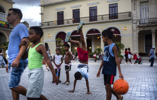 In this November 10, 2019 photo, a youth does hand stands amid pedestrians in a square in Old Havana, Cuba. (Photo by Ramon Espinosa/AP Photo)
