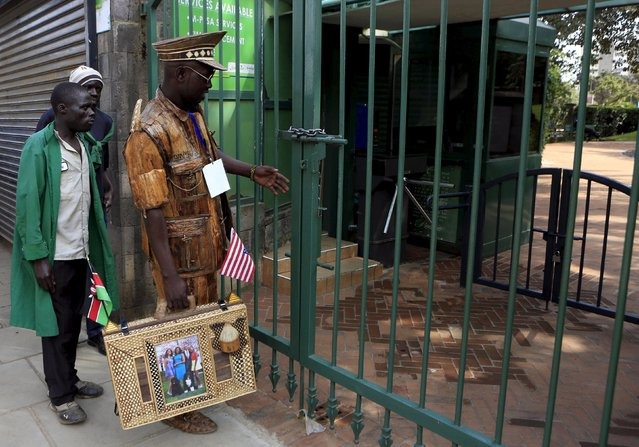 A man wearing a suit and carrying a briefcase made from the dried bark and leaves of a banana tree arrives at the Memorial Park to pay his respects shortly after U.S. President Barack Obama laid a wreath in honor of those who died after an al Qaeda attack in 1998 at the compound of the former U.S. Embassy in Kenya's capital Nairobi July 25, 2015. (Photo by Noor Khamis/Reuters)