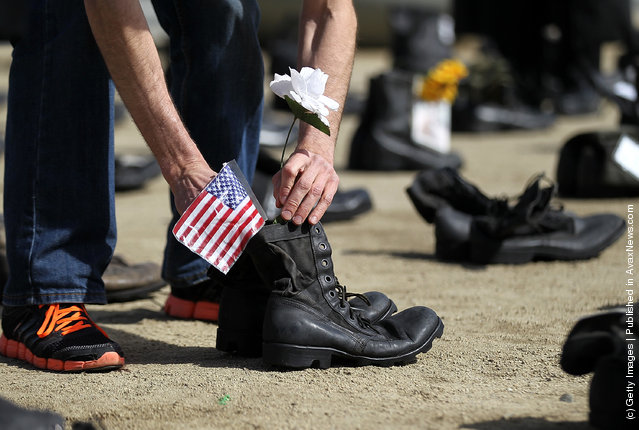 An Iraq war veteran placed an American flag in a pair of combat boots that are part of the Eyes Wide Open exhibit in front of San Francisco City Hall