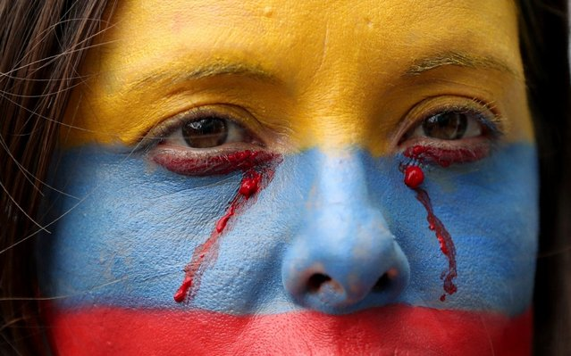 In this November 27, 2019 photo, an anti-government demonstrator, her face painted with the colors of the Colombian national flag, takes part in a protest, in Bogota, Colombia. Thousands of people have protested in Colombia over the past week, voicing discontent with the government of President Ivan Duque. (Photo by Fernando Vergara/AP Photo)