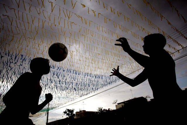 Boys play ball May 23, 2014 in a street decorated for the upcoming World Cup in Brasilia, one of the host cities for the international soccer tournament that starts in June. (Photo by Eraldo Peres/Associated Press)