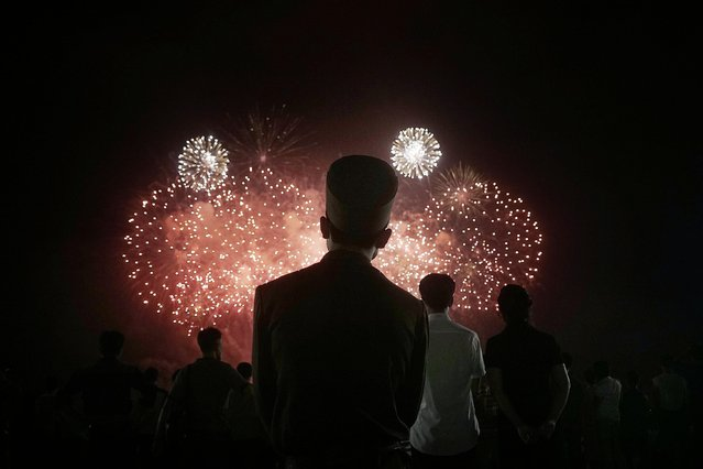 A North Korean soldier watches as fireworks explode, Monday, July 27, 2015, in Pyongyang, North Korea as part of celebrations for the 62nd anniversary of the armistice that ended the Korean War. (Photo by Wong Maye-E/AP Photo)