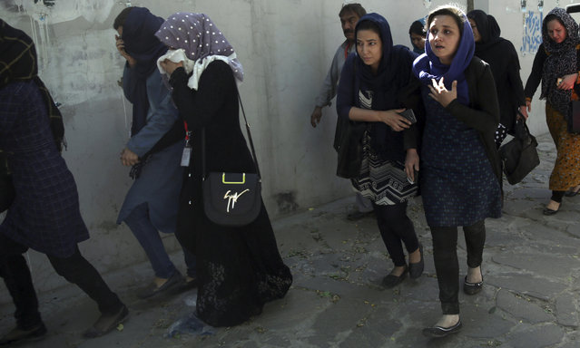 Roshan mobile company employees leave the site of a suicide attack in Kabul, Afghanistan, Wednesday, May 31, 2017. (Photo by Massoud Hossaini/AP Photo)