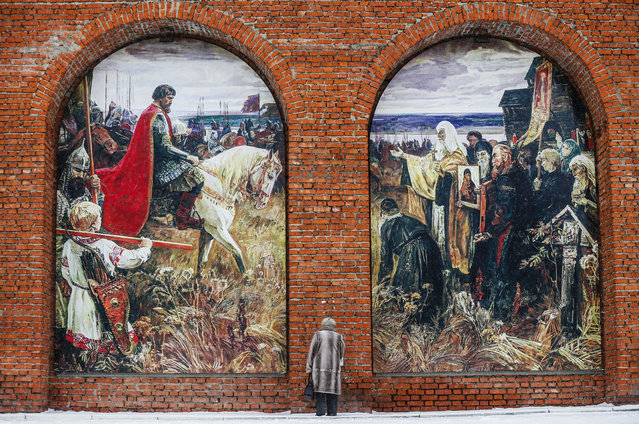 """Russian woman stands in front of the wall of the Kolomna Kremlin with huge painting of """"Dmitry Donskoy assembles an army against the Tatars"""" in Kolomna, Russia, 12 February 2016. Kolomna Kremlin was built by the order of Russian tsar Vasily III from 1525-1531 to imitate the Moscow Kremlin. (Photo by Sergei Ilnitsky/EPA)"""