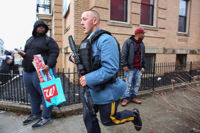 Police officers arrive at the scene of an active shooter in Jersey City, New Jersey, on December 10, 2019. One officer was shot when two gunmen with a long rifle opened fire in Jersey City, New Jersey, on the afternoon of December 10, 2019 , according to two officials. Two suspects were barricaded in a convenience store, the officials said. One officer was being taken to a nearby hospital. (Photo by Kena Betancur/AFP Photo)