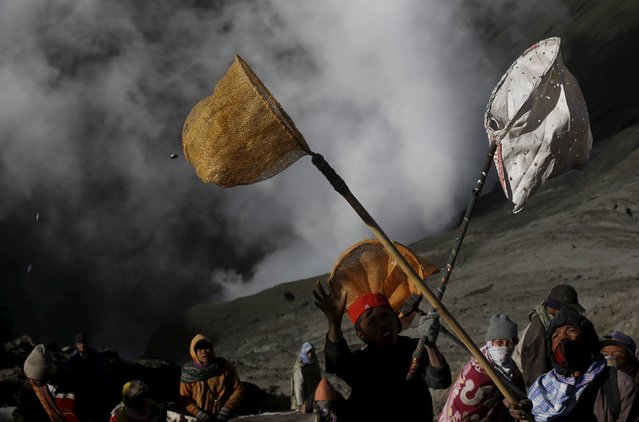 Villagers hold nets in an attempt to catch coins thrown as offerings by Hindu worshippers into the crater during the Kasada Festival at Mount Bromo in Probolinggo, Indonesia's East Java province, August 1, 2015. (Photo by Reuters/Beawiharta)