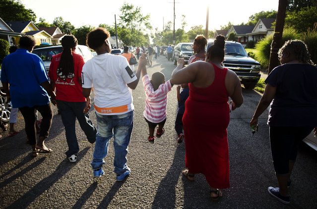 Michaele Lee Jr., 4, center, is swung by his mother Chinquenta Bell, right, and aunt Shaquenta Bell, during a procession down the street where Muhammad Ali grew up following a community memorial service outside his childhood home Monday, June 6, 2016, in Louisville, Ky. In a city accustomed to capturing the world's attention for just two minutes during the Kentucky Derby each year, Ali's memorial service Friday looms as one of the most historic events in Louisville's history. Former presidents, heads of nations from around the globe, movie stars and sports greats will descend upon the city to pay final respects to The Louisville Lip. (Photo by David Goldman/AP Photo)