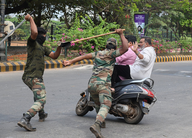 Members of the Karnataka Reserve Police Force swing their sticks to beat two men on a scooter who rode too close to a barricade set up on a street in Mangalore on December 20, 2019, amid heightened security due to protests over India's new citizenship law. Fresh clashes between Indian police and demonstrators erupted on December 20 after more than a week of deadly unrest triggered by a citizenship law seen as anti-Muslim. (Photo by AFP Photo/Stringer)