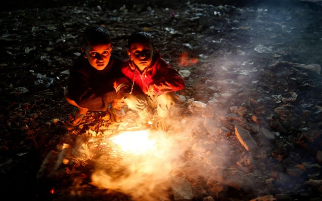 Bangladesh children to keep warm themselves by setting rubbish on fire at night during a cold wave grips in Dhaka, Bangladesh 20 December 2019. According to the Met office a mild cold wave sweeping across the county in Bangladesh. (Photo by Monirul Alam/EPA/EFE/Rex Features/Shutterstock)