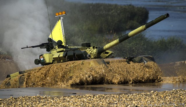 An Indian tank emerges from the water during competition in Alabino, outside Moscow, Russia, Monday, August 3, 2015. (Photo by Pavel Golovkin/AP Photo)