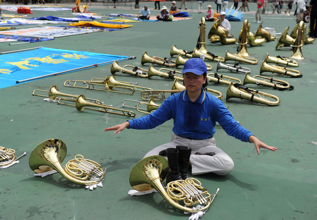 """A member of a Falun Dafa band relaxes before a pro-democracy rally seeking greater democracy in Hong Kong on July 1, 2014 as frustration grows over the influence of Beijing on the city. July 1 is traditionally a day of protest in Hong Kong and also marks the anniversary of the handover from Britain to China in 1997, under a """"one country, two systems"""" agreement. (Photo by Dale de la Rey/AFP Photo)"""