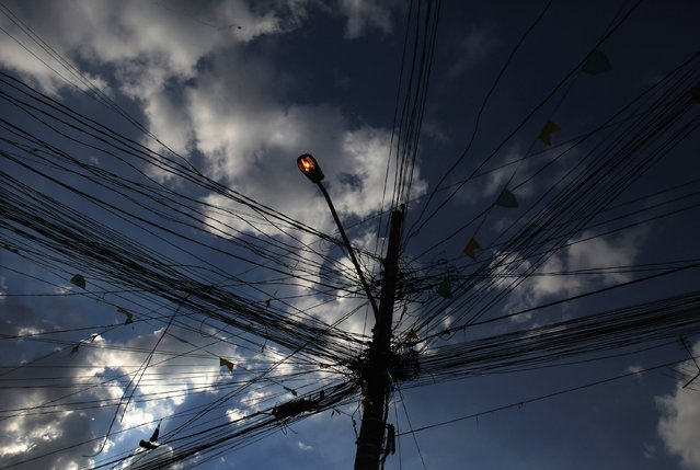"""A street light is surrounded by electric cables at the Corrilhos slum in Sao Paulo, on June 23, 2014. In a project called """"On The Sidelines"""" Reuters photographers share pictures showing their own quirky and creative view of the 2014 World Cup in Brazil. (Photo by Nacho Doce/Reuters)"""