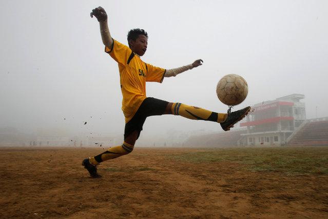 A boy kicks a soccer ball during a practice at a stadium on a foggy morning in Agartala, India, November 17, 2016. (Photo by Jayanta Dey/Reuters)