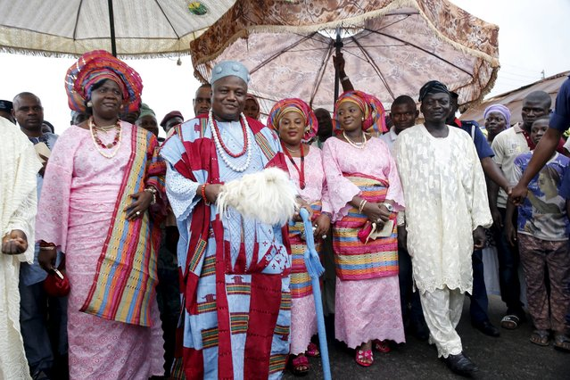 Monarch of Osogbo, Oba Jimoh Oyetunji (2nd L) walks with his wives down a street during the traditional town cleansing procession at the start of the annual Osun festival in Osogbo in Nigeria's southwest, August 10, 2015. (Photo by Akintunde Akinleye/Reuters)
