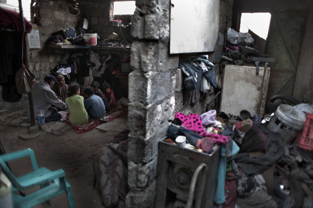 In this Monday, June 20, 2016 photo, a Palestinian family breaks their Ramadan fast in their house in el-Zohor slum, on the outskirts of Khan Younis refugee camp, southern Gaza Strip. (Photo by Khalil Hamra/AP Photo)
