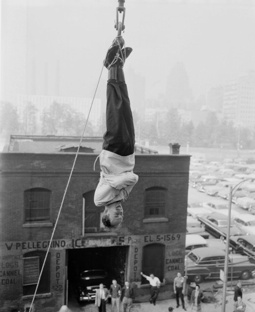 The Amazing Randi, 27-year-old Canadian escape artist is suspended in the air with the help of a crane, June 7, 1956 in New York, at 49th St. and First Avenue. He was tied in a strait jacket and escaped in 1 minute, 40 seconds. (Photo by Anthony Camerano/AP Photo)