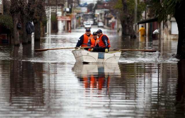 Argentine policemen patrol a flooded street on a boat in Lujan, Argentina, August 12, 2015. Over 20,000 people have been evacuated after torrential rains in the last weekend caused rivers to rise and flood cities in northern Buenos Aires province, local media reported. (Photo by Marcos Brindicci/Reuters)