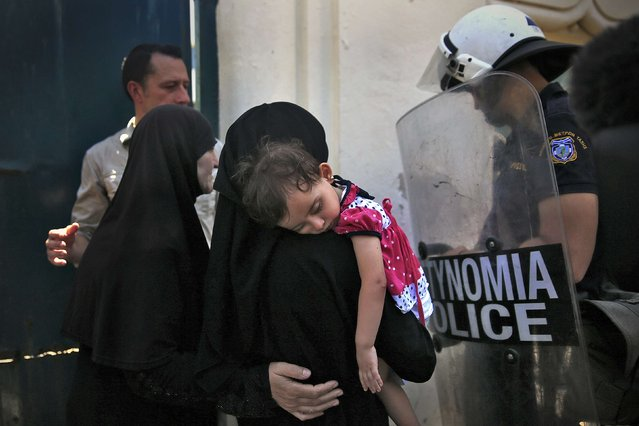 A Syrian refugee holds her daughter as she waits to enter the national stadium for a registration procedure at the Greek island of Kos, August 13, 2015. (Photo by Alkis Konstantinidis/Reuters)