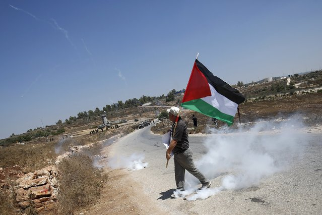 A Palestinian protester holds a Palestinian flag as he walks next to a tear gas canister fired by Israeli troops during clashes at a protest in solidarity with Palestinian detainee Mohammed Allan, in the West Bank village of Nabi Saleh, near Ramallah August 14, 2015. (Photo by Mohamad Torokman/Reuters)