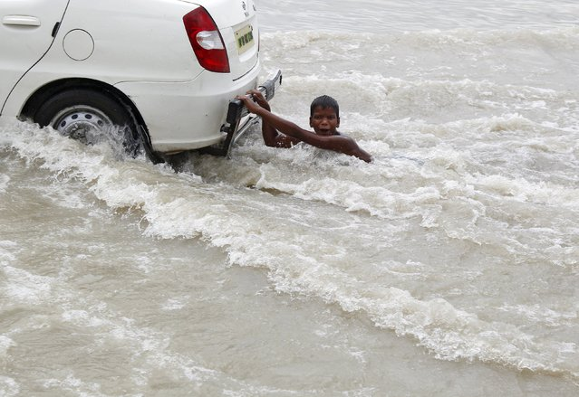 A boy plays as he holds onto a taxi through the flooded banks of river Ganges after a heavy downpour caused the rise in water levels in the river in Allahabad, India August 18, 2015. (Photo by Jitendra Prakash/Reuters)