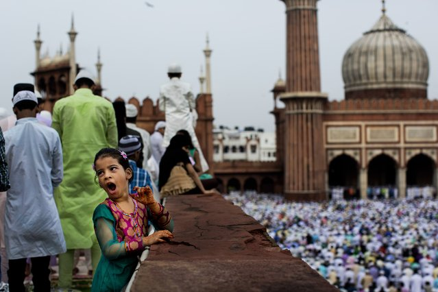 A young Indian Muslim yawns during Eid al-Fitr prayers at the Jama Masjid mosque in New Delhi, Tuesday, July 29, 2014. Millions of Muslims across the world are celebrating the Eid al-Fitr holiday, which marks the end of the month-long fast of Ramadan. (Photo by Bernat Armangue/AP Photo)