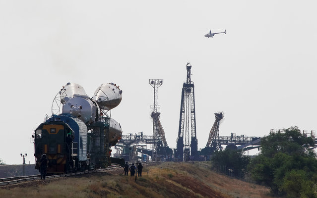 A police helicopter flies by the Soyuz MS spacecraft for the next International Space Station (ISS) crew of Kate Rubins of the U.S., Anatoly Ivanishin of Russia and Takuya Onishi of Japan as it is transported from an assembling hangar to the launchpad ahead of its launch scheduled on July 7, at the Baikonur cosmodrome in Kazakhstan July 4, 2016. (Photo by Shamil Zhumatov/Reuters)