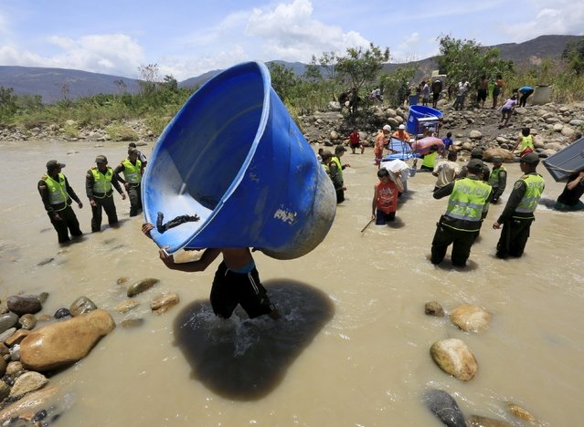 People carry their belongings while crossing the Tachira river border with Venezuela into Colombia, near Villa del Rosario village August 25, 2015. (Photo by Jose Miguel Gomez/Reuters)
