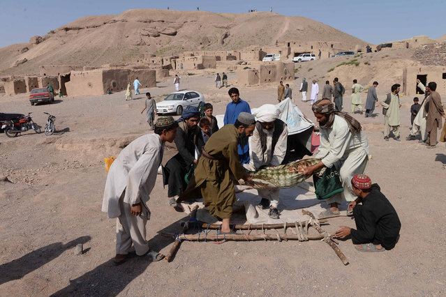 Afghan men carry the body of a victim after a series of explosions at a gas storage facility on the edge of the western city of Herat on August 25, 2015. At least 11 people including several children were killed in a series of explosions at a gas storage facility on the edge of the western city of Herat, officials said on August 25. The explosions triggered an inferno which spread to a nearby camp for internally displaced people where most of the deaths occurred. (Photo by Aref Karimi/AFP Photo)